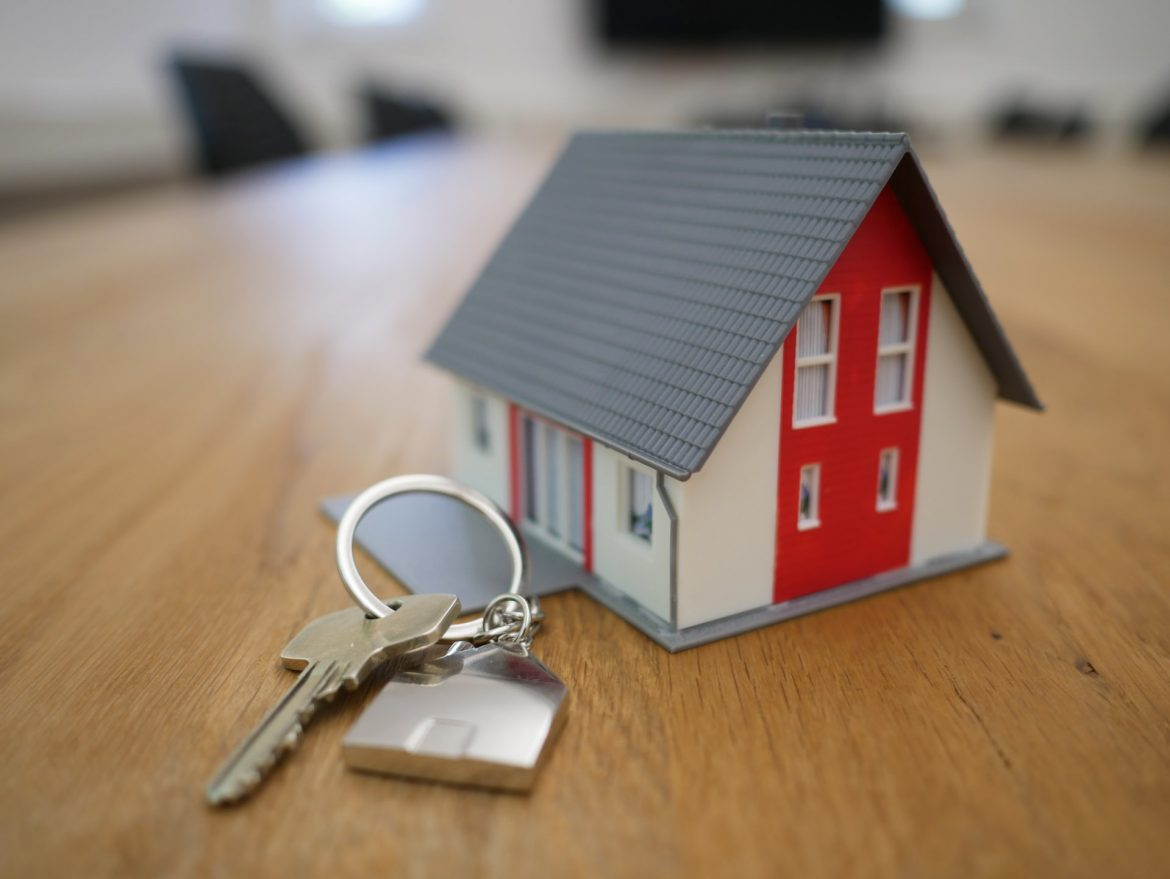 A key and small model of a house on the table