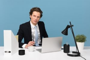 A man in a suit in front of a laptop.