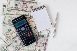 A calculator, a notebook, and dollar bills