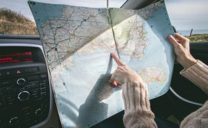 A woman planning a move to Arizona while pointing at a map and sitting in the car