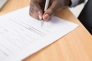 A person signing an agreement about selling a house