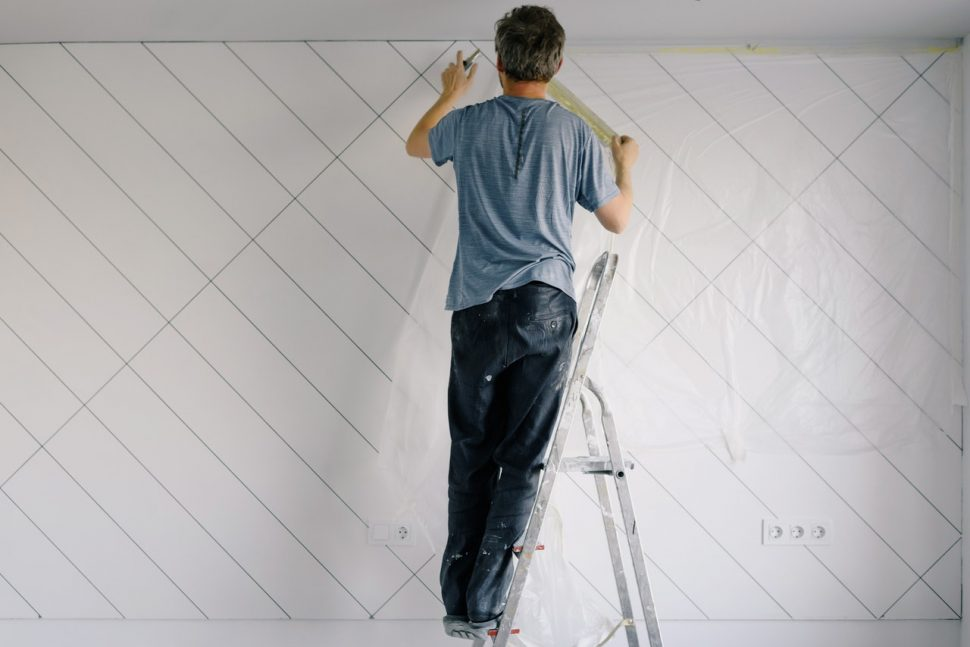 A man on a ladder painting a wall.