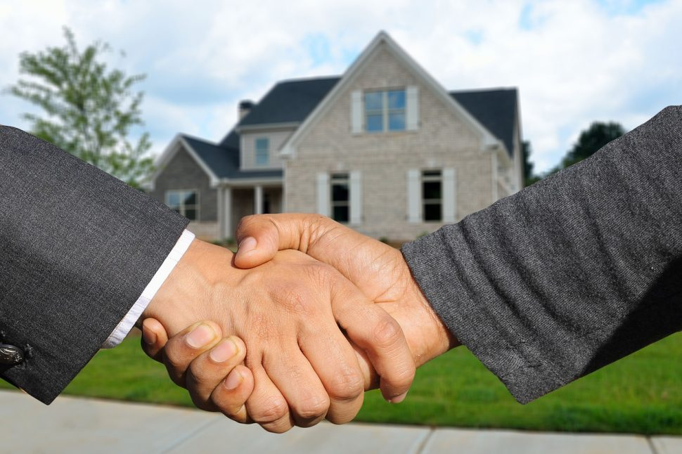 A handshake between two people with a view of a house in the background