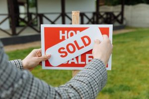 A person placing a sold sticker on a for sale sign in front of a house